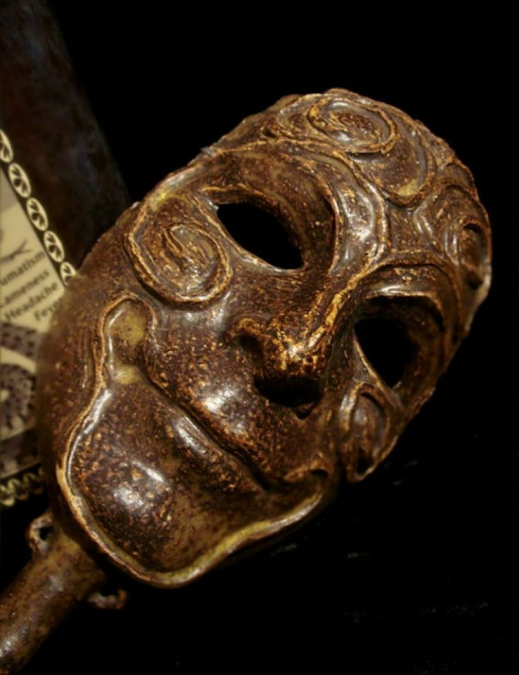 Old grinning clay mask with handle for sale by Gothic Rose Antiques at MoreThanHorror.com