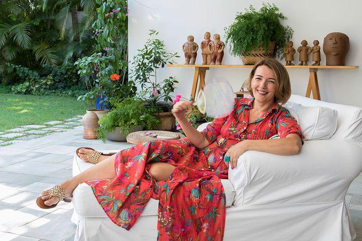 Decoração com personalidade, decoração colorida com obras de arte e varanda com sofá branco.