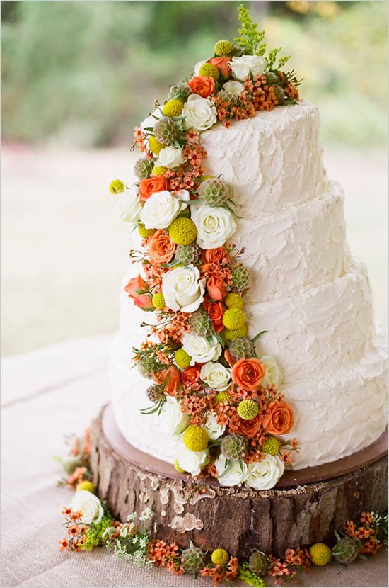 rustic white wedding cake with yellow, orange and green flower accents   photo: www.jhendersonstudios.com