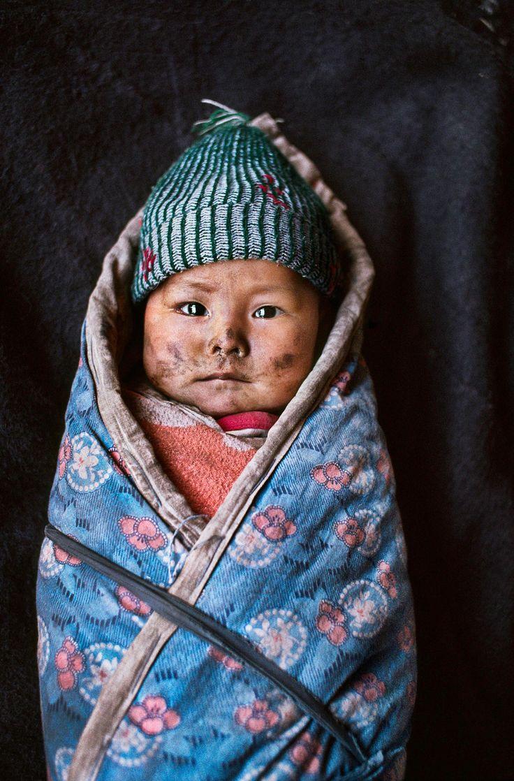 Tibet, Ville de Xigaze (Shigatsé) - Jeune enfant tibétain emmailloté - Source : Steve McCurry, photographe américain (1950-20--) / Galerie d'images - Membre de l'Agence Magnum depuis 1986, il parcourt le monde à la recherche de ce qu'il appelle « l'inattendu, le moment du hasard maîtrisé, qui permet de découvrir par accident des choses intéressantes que l'on ne cherchait pas. » Il est très connu pour sa photographie en couleur très évocatrice, dans la tradition du reportage documentaire -