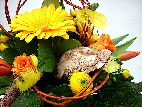 """Ritzka Blumengroßhandel: Strauß Sonnengelb: Endlich wieder die Sonne genießen! Auch wenn sich der Frühling in diesem Jahr etwas mehr Zeit lässt – mit unserem Strauß-Tipp """"Sonnengelb"""" lassen Sie bei Ihren Kunden mit Sicherheit die Sonne strahlen. Eine Komposition warmer Gelb- und Orangetöne dominiert diesen Frühlingsstrauß aus Tulpen, Rosen, Ranunkeln und Gerbera. Die gelben Federn verleihen dem Strauß zudem einen österlichen Touch."""