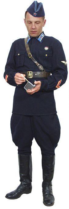 """Майор одет в темно-синюю пилотку , темно-синюю гимнастерку с нарукавными знаками различия обр. 1940 года. и знаком летного состава ВВС на левом рукаве, темно-синие брюки """"бриджи"""", сапоги, повседневное снаряжение командного и начальствующего состава."""