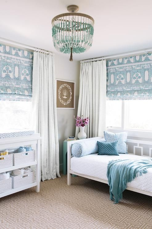 Illuminated by a blue beaded chandelier, this white and blue girl's bedroom features a West Elm Window Daybed placed on a taupe maze rug and dressed in white bedding accented with a blue throw blanket and blue pillows.
