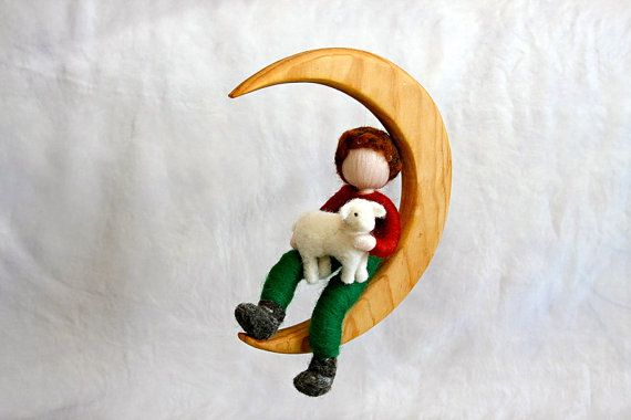 This is a Waldorf inspired piece made of wool by the needle-felting technique, placed on a half-moon made of wood with a beeswax coating. Its been