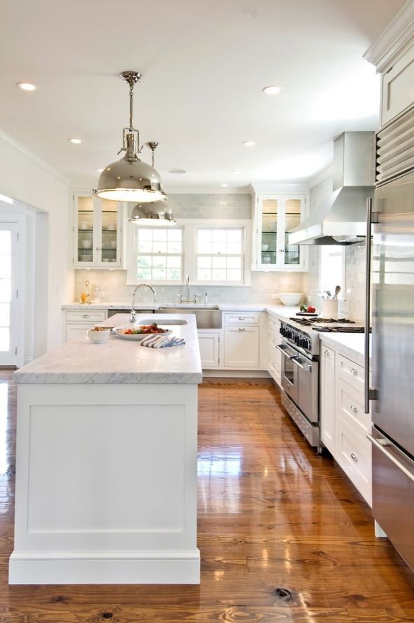 Love this white kitchen with the warm wood floors & those metal light fixtures!