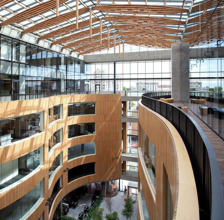 The Atrium by D'Ambrosio Architecture & Urbanism in Victoria, BC, Canada. A seven-storey atrium introduces daylight into the heart of the complex while enlivening the street at night. The use of wood as an interior finish is maximized in what is otherwise non-combustible construction. Panelized hemlock grilles follow the sweep of the atrium's curving walls and tongue and groove western red cedar soffits over the sidewalk bring warmth and definition to the public space around the building.