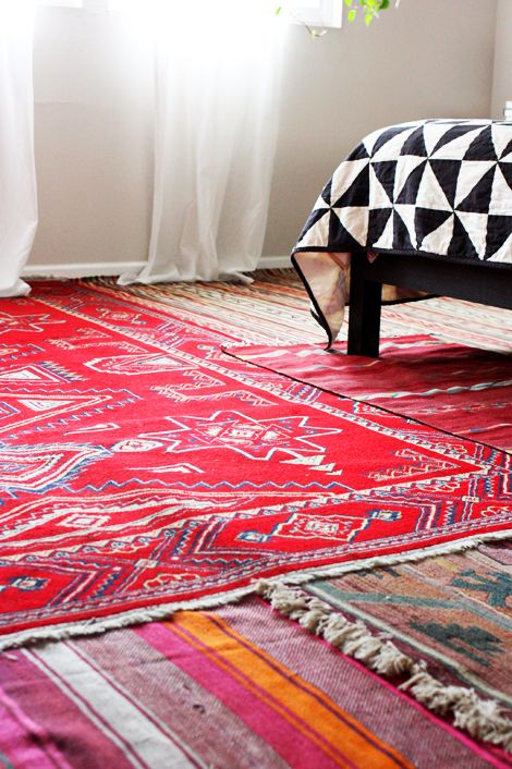 Awesome idea for layering rugs to conceal carpet in a bedroom!