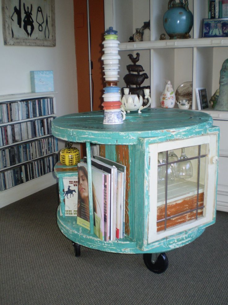 Cable reel spool repurposed into a coffee table with a wine rack, book & magazine rack, shelves and of course a cupboard to hold glasses in an overhead rack with an accoutrements drawer.