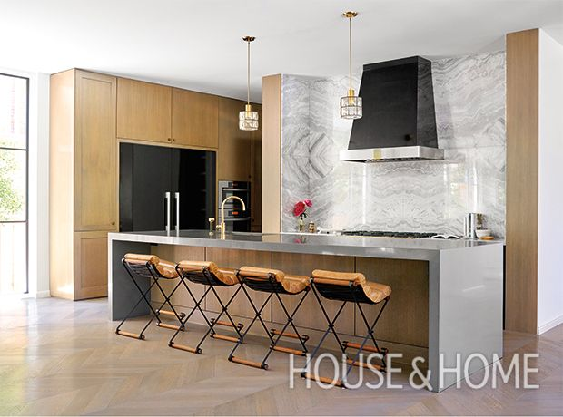 In this kitchen, luxurious Himalayan white marble backsplash return wraps around the cooking area and contrasts the black hood. | Photographer: Nathan Schroder | Designer: Lloyd Ralphs Design