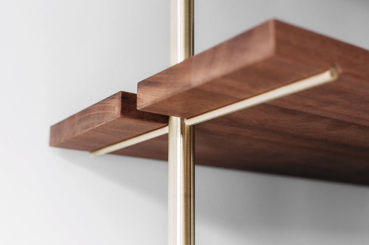 You might not think of bookshelves as décor centerpieces, but that's only because you haven't seen the Brass Rail Shelving system yet. Think golden brass bars paired with rich brown wood and a splash of minimalism.
