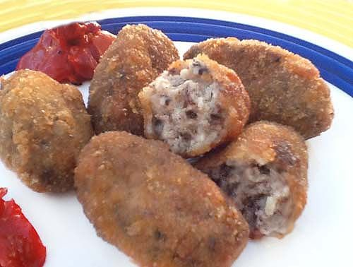 Para las croquetas: 1 morcilla ibérica grande (200 gr) - 1 puñado de piñones - Media cebolla pequeña - 3 cucharadas soperas colmadas de harina - 1 vaso de leche - 1 vaso de caldo de pollo o carne - Sal, pimienta, un golpe de clavo de olor molido y nuez moscada - Pimientos del piquillo (opcional) - Aceite de oliva virgen extra - Perejil picado