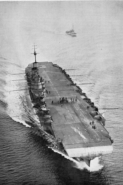 Illustrious    HMS Illustrious cutting through the water at speed to enable aircraft to land on her deck. This WWII photo( taken in the period 1940-1942) was taken just after a Swordfish had made a landing. The deck crew are taking it to the forward lift.