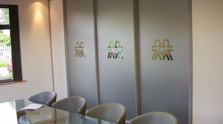 Full frosted glass panels with cut out logo by Space3.co.uk