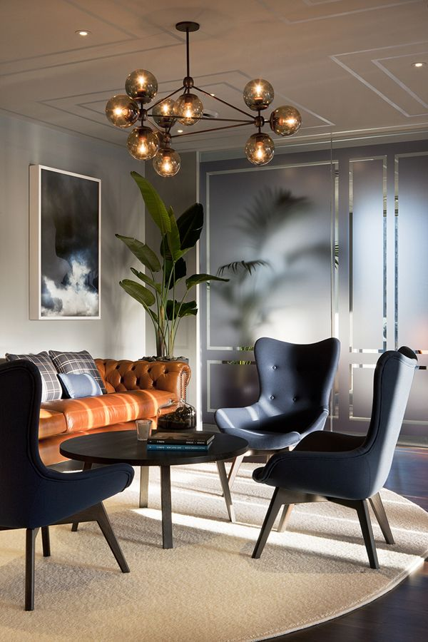 elegant modern living room with glass globe chandelier love the cognac leather sofa mix with charcoal gray chairs via escala partners