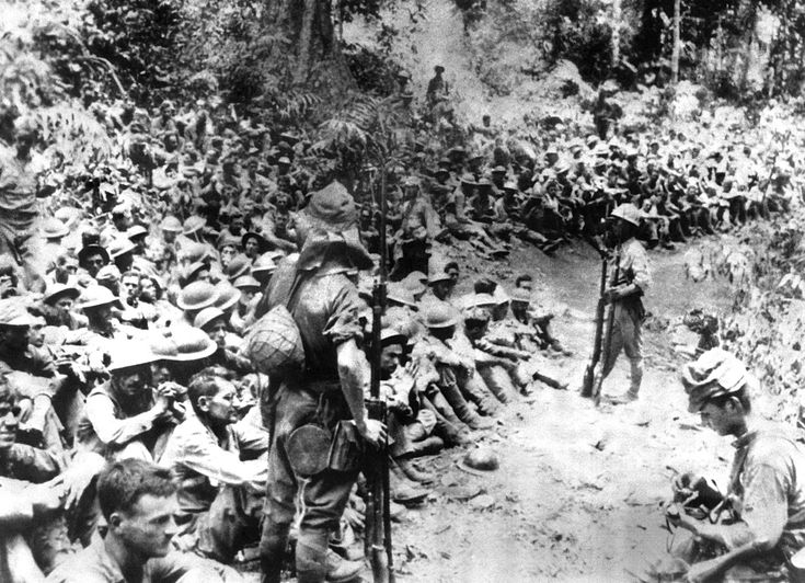 """Japanese soldiers stand guard over American war prisoners just before the start of the """"Bataan Death March"""" in 1942. This photograph was stolen from the Japanese during Japan's three-year occupation. (AP Photo/U.S. Marine Corps)"""