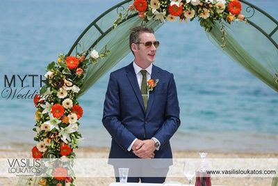 Groom awaits for his love - beautiful sea backdrop - flower arch with burnt orange - white & olive green flowers #weddingflowers #groomphotos #weddingceremony_beachwedding_flowerarch