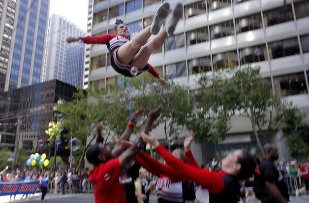 Courtney Sanford of the contingent Cheer San Francisco is thrown in the air as the group marches down Market Street in the San Francisco, Sunday June 26, 2011, in San Francisco, Calif.