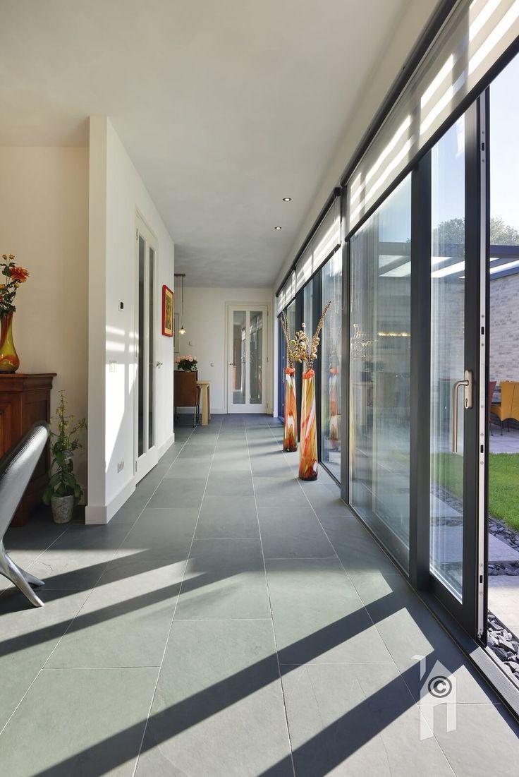 Lessenaarswoning, het huis heeft een goed contact met de tuin, dat is met de lange 'laan' van glazen puien en aluminium kozijnen perfect geslaagd.