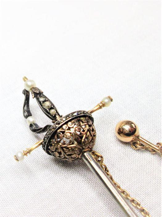 Gouden degen reverspeld met zaadparels en roosgeslepen diamanten ca. 1840  Gouden zwaard reverspeld/hoedenspeld met zaadparels en roos geslepen diamanten.Afmetingen zwaard: lengte 104.7 mm - breedte: 27.2 mm - dikte: 12.5 mm.Parels: 3.1 mm rond - 2.7 mm rond - 2 mm rond.Diamant: 2 mm rond.Leeftijd ca. 1840Speld: lengte 58.9 mm. Balletje: 5.4 mm rond.Ketting: lengte 7 cm - schakels ca. 1.4 mm.Is gemerkt met: keurteken en getoetst op 18 karaat goud..Gewicht: 7.12 gramVerkeert in goede conditie…