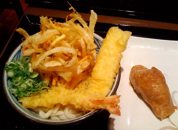 Kyoto Best Cheap Eats: Marugame Udon Noodle Restaurant 京都 丸亀製麺 Marugame Seimen is conveniently located in the bustling Sanjo-Kawaramachi neighborhood and offers Kyoto's best cost performance for tasty, filling and healthy meals. Marugame serves udon noodle dishes and the udon is actually made fresh, right on the premises! No 'Made in China' and 'Defrosted in Kyoto' budget noodle dishes here!