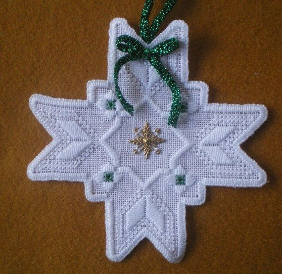 I hand stitched this sweet 4 1/2 Hardanger Star needlework piece on white linen with white perle cotton thread. It has a brass snowflake charm with green