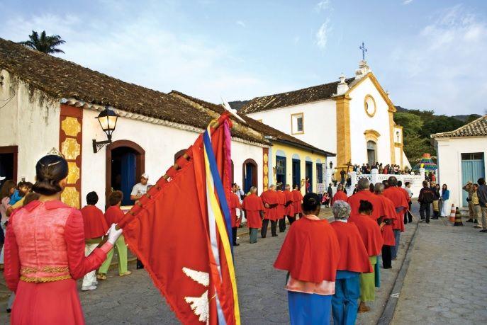 A bandeira do Divino e os músicos. Na frente do cortejo, alguém leva uma bandeira vermelha, que ao centro tem uma pomba branca para representar o Espírito Santo.