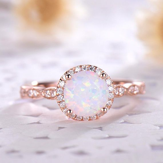 This is an opal engagement ring rose gold. The stones are natural Opal and VVS man made cz diamond. The center opal is about 7mm Round Cut. The stones can be replace with other gemstones.For example,if you dont like the CZ accent,you can ask me replace it with