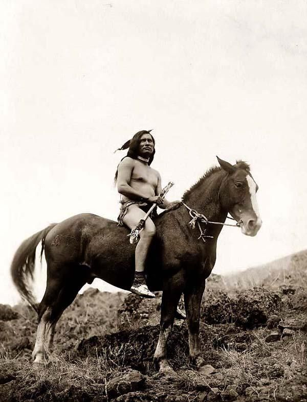 Here we present an historic image of an Old-time Nez Perce Indian Warrior. It was taken in 1910 by Edward S. Curtis.    The image shows a Nez Perce Warrior wearing a loin cloth and moccasins, on horseback.    We have created this collection of images primarily to serve as an easy to access educational tool. Contact curator@old-picture.com.    Image ID# 75A03285