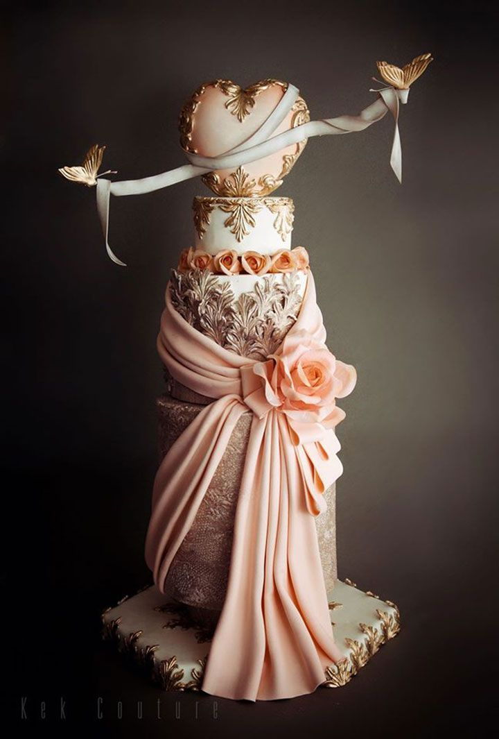 Over the top wedding cake with gold acanthus leaves, peachy pink draped fabric and roses and that ribbon wrapped heart topper with suspended butterflies = perfection