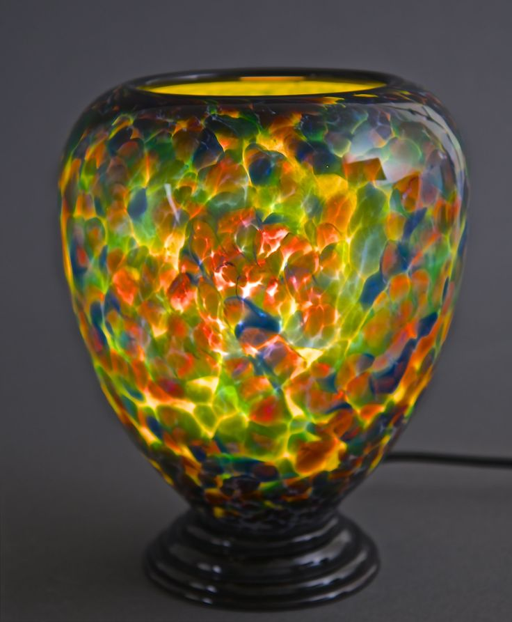 Multi Color Table Lamp by Curt Brock. This is a hand blown glass lamp that has black trim on top and black foot. When lit, it has a warm luminescent quality. During the day, it is a beautiful object on its own and at night it comes to life. Each piece is unique. Dimensions and pattern will vary slightly. Takes one 90-watt (maximum) incandescent or compact fluorescent bulb (not included).
