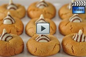 Peanut Blossom Cookies consist of a peanut butter cookie that has a chocolate Kiss sitting happily on top.  From Joyofbaking.com With Demo Video