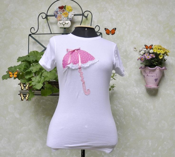 Camiseta branca, marca HERING, tamanho Médio, mangas curtas, decote redondo, com patch aplique de uma sombrinha rosa.  Detalhes:aplicação de renda, trancelim e fita.    **** PRODUTO PRONTA ENTREGA****  ...