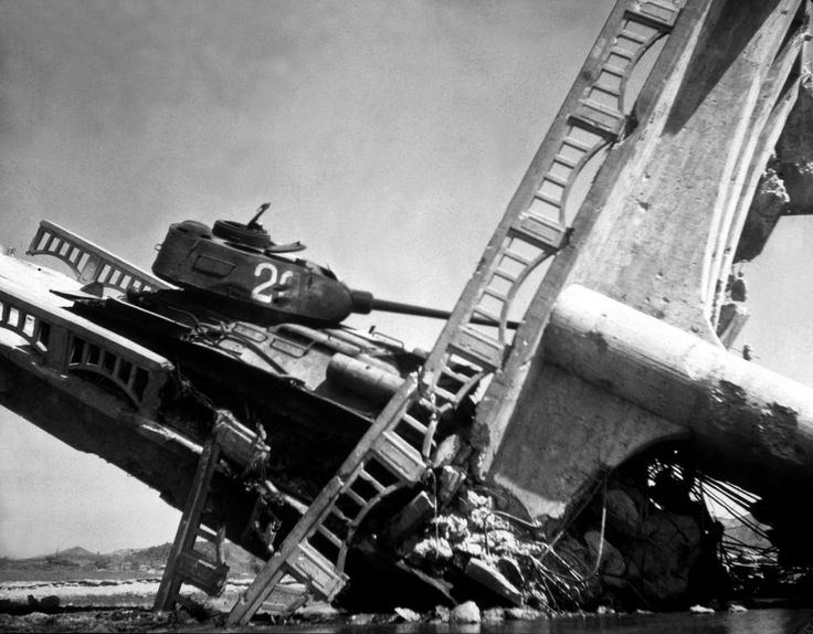 The wreckage of a bridge and North Korean Communist tank south of Suwon, Korea. The tank was caught on a bridge and put out of action by the Air Force. October 7, 1950. Marks. (Army) NARA FILE #: 111-C-6143 WAR & CONFLICT BOOK #: 1499