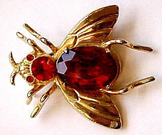 This is a figural gold bee or fly pin with faceted red stones for body, head and eyes.  Marked Coro with the Pegasus which is a 1945 Coro jewelry mark.  In very good condition. There is a hole on the tip of one wing so this may be one part of a dual set.