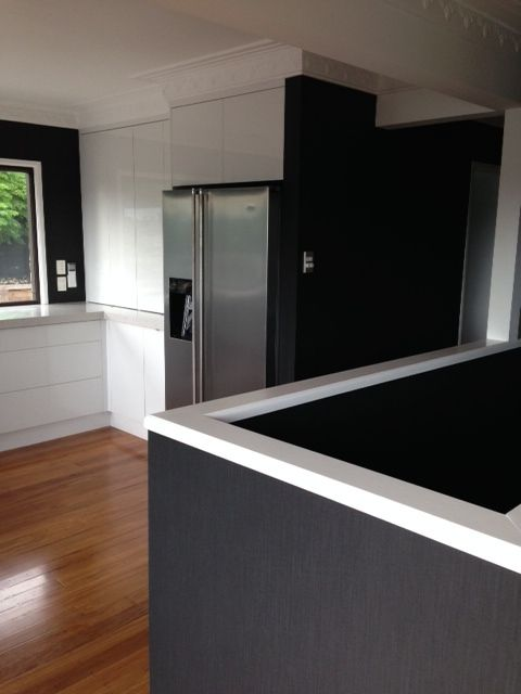 A striking combination of black and white gave this once dated kitchen a fresh new look for this Howick home #wallpaper #black #white #gloss #kitchen #stainless #interiordesign #designer #timber