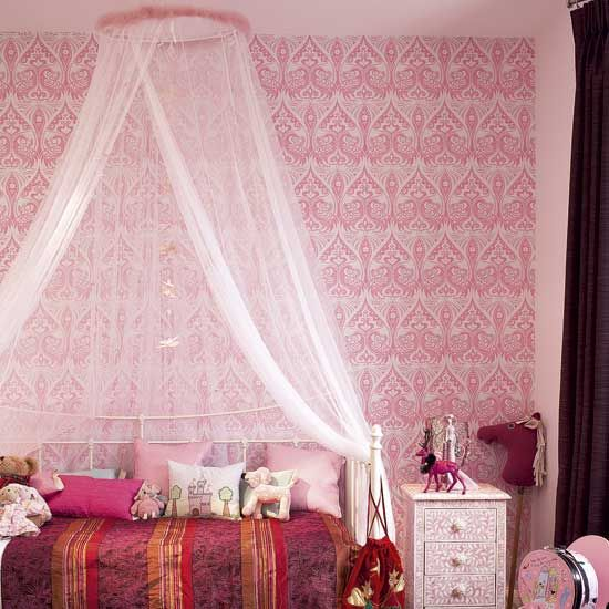 Wow look at this wallpaper! Detailed pink wallpaper gives this girl's bedroom a grown-up feel. The netting, from IKEA, over the bed creates a princess-like haven, while layered cushions make it cosy.
