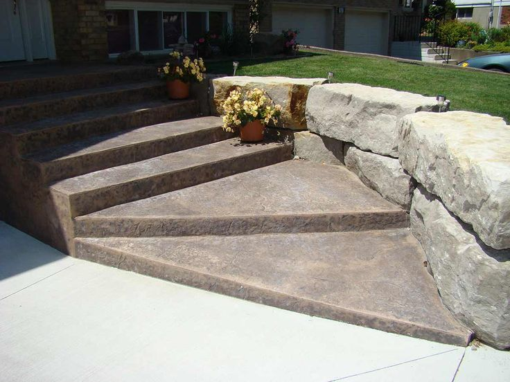 Stamped, coloured decorative concrete steps and an Armour stone retaining wall add an impressive entrance to this home.