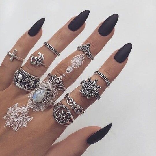 Black matte almond shaped nails with lots of rings