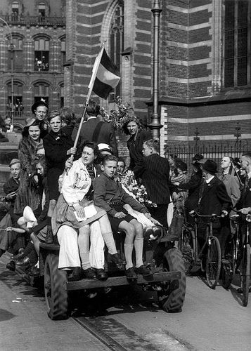 Liberation of Holland. A Jeep loaded with celebrating people holding a Dutch flag riding alongside the 'Nieuwe Kerk'-church to Dam square, Amsterdam, The Netherlands. May 8, 1945.