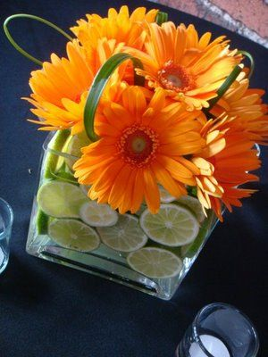 Bright colored daisies in square glass vases with sliced limes.