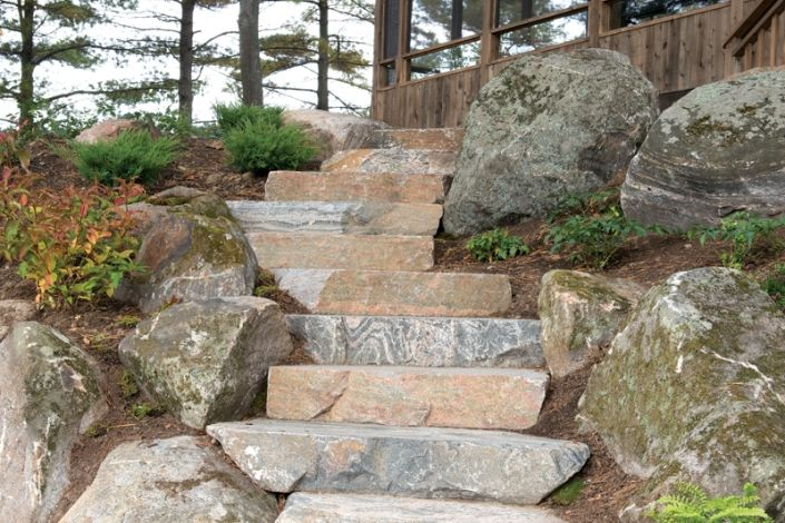 """A calibrated 7"""" rise of  Rosseau Quarry granite stone treads were used to twist this pathway down through the existing natural landscape. Random stair treads from Muskoka Rock Company are often deeper from front to back. This allows the installer to easily turn the direction of the feature allowing for a more functional and natural finished product."""