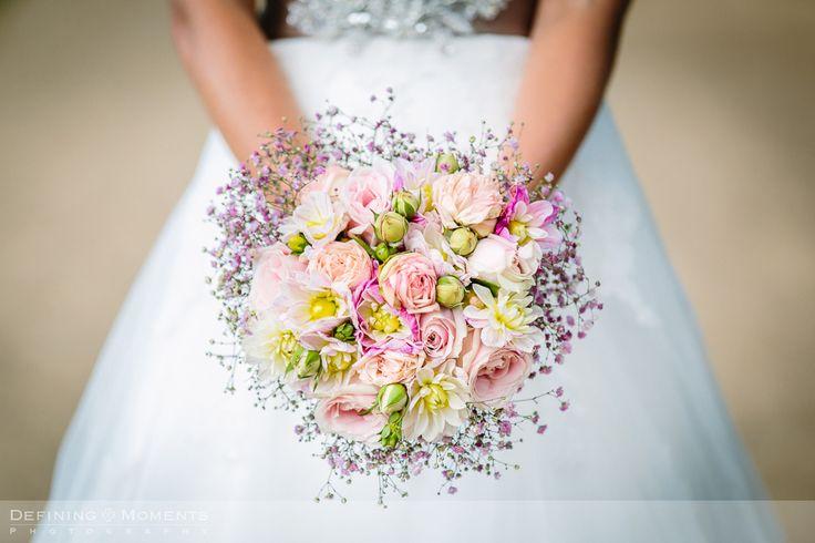 Bruidsboeket in zachte, roze pasteltinten: roze, zalmroze, crème en zachtpaars met rozen, dahlia en gipskruid.