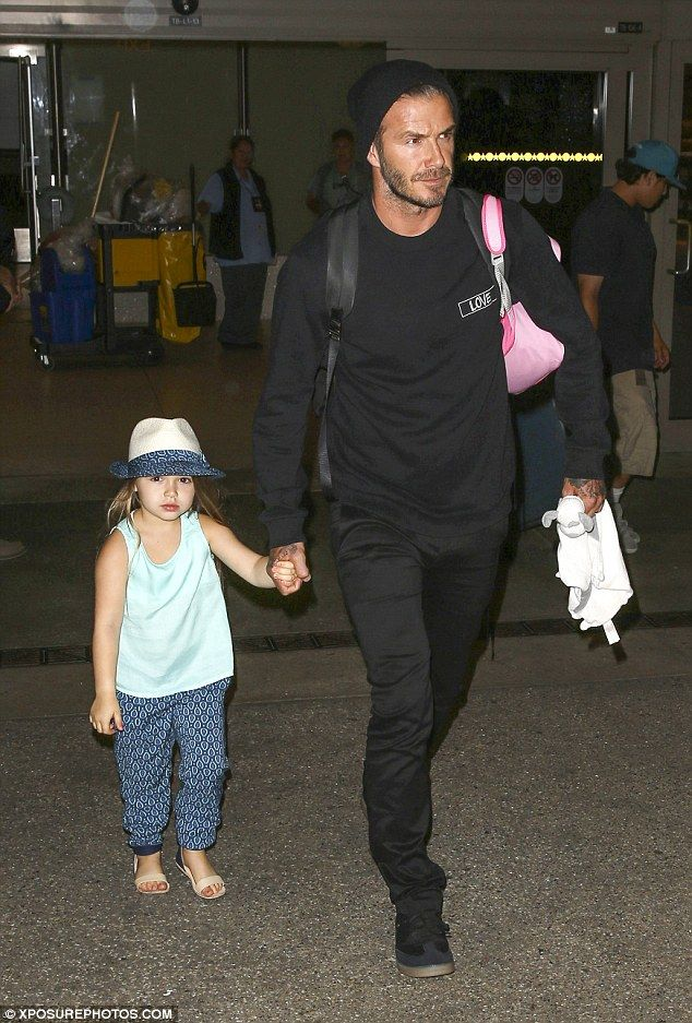 Proud father: David Beckham arrived at LAX airport on Sunday, leading his daughter Harper ...