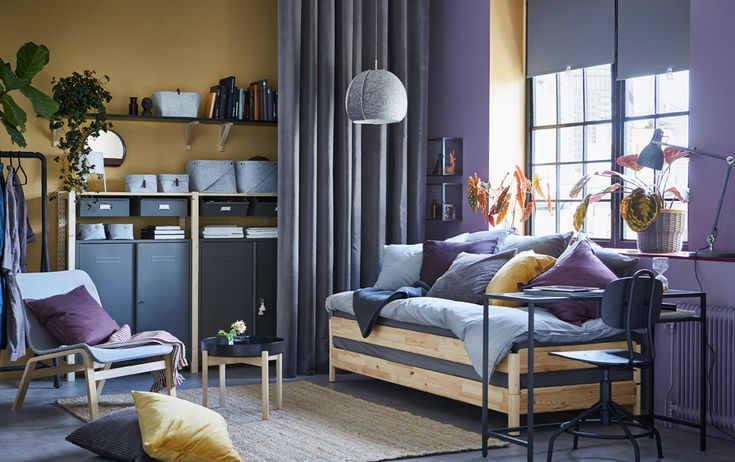 A yellow and purple studio apartment with a practical pine UTÅKER sofa bed which can be used as a sofa, single, double or twin beds. The IVAR storage in wood with cabinet units in grey steel can be seen in the backgrounds.