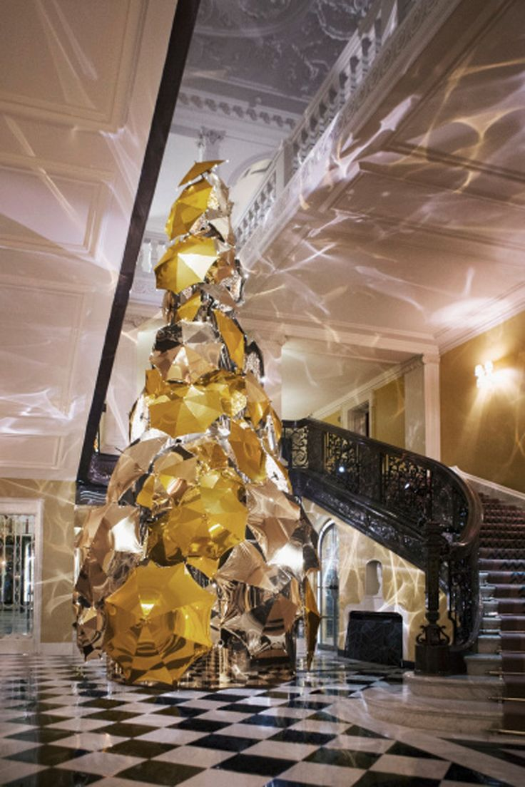 The Claridge's Christmas tree is unveiled, which this year is designed by Burberry's Christopher Bailey and features 100 gold and silver metallic umbrellas and 77,000 lights