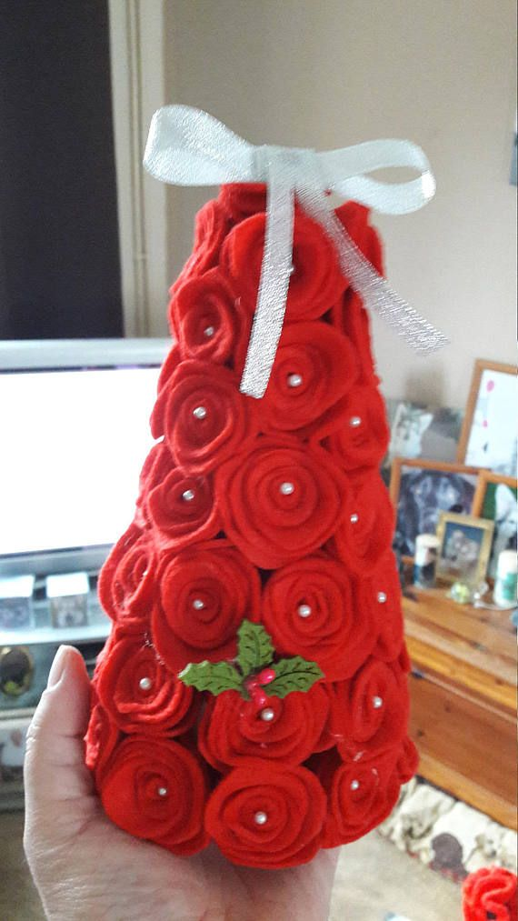A red felt rose tree/cone with pins in the centre. With a holly on and ribbon