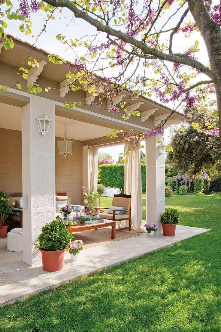 Porche con butacas y maceteros junto al césped del jardín_00323548 1