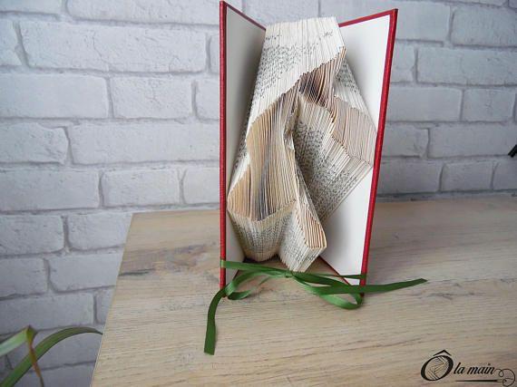 La collection A Livre Ouvert est une série de livres doccasion transformés en objets de décoration via plusieurs techniques (découpage, pliage ou décou-pliage). Chaque page est découpée et/ou pliée à la main pour donner vie à un motif.  Le modèle Comme chien et chat est un livre plié pour représenter la silhouette dun chat et dun chien. Le livre possède une magnifique couverture bordeaux et verte. VENDU SEUL