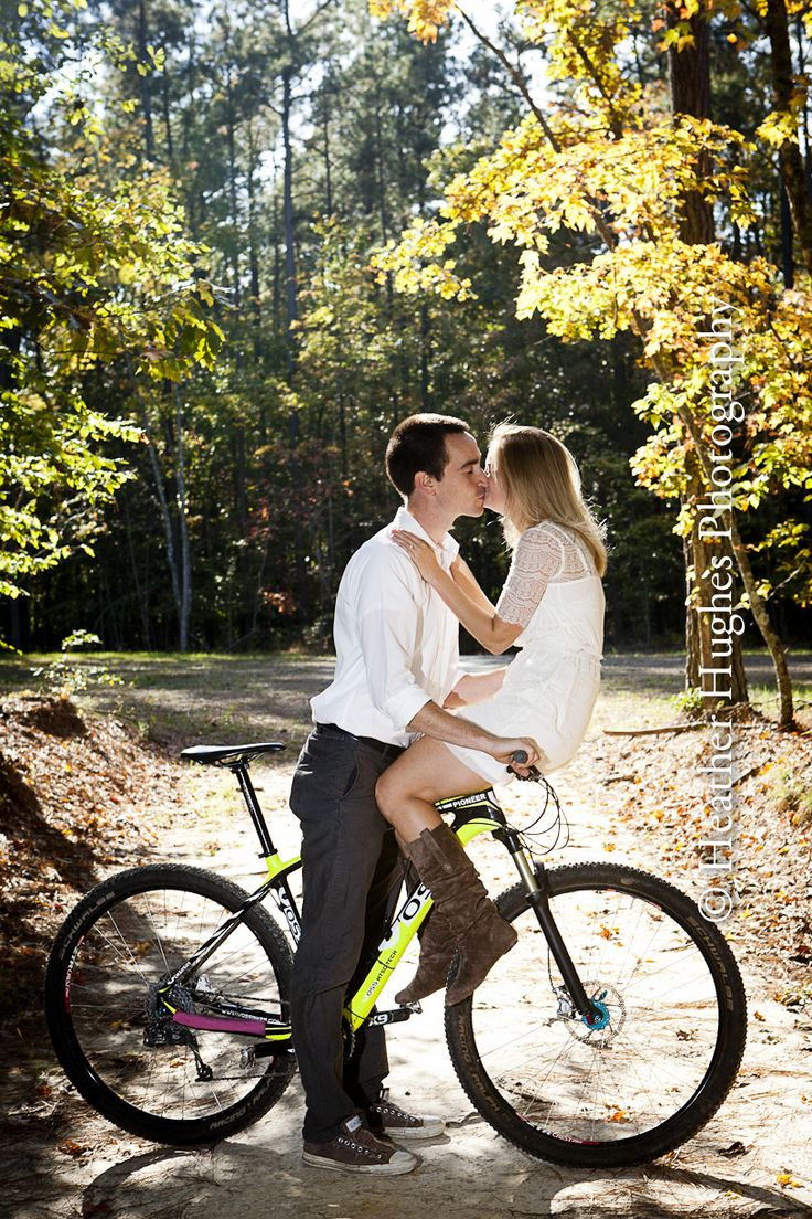 Fun engagement portrait on a mountain bike in the woods by Heather Hughes Photography.