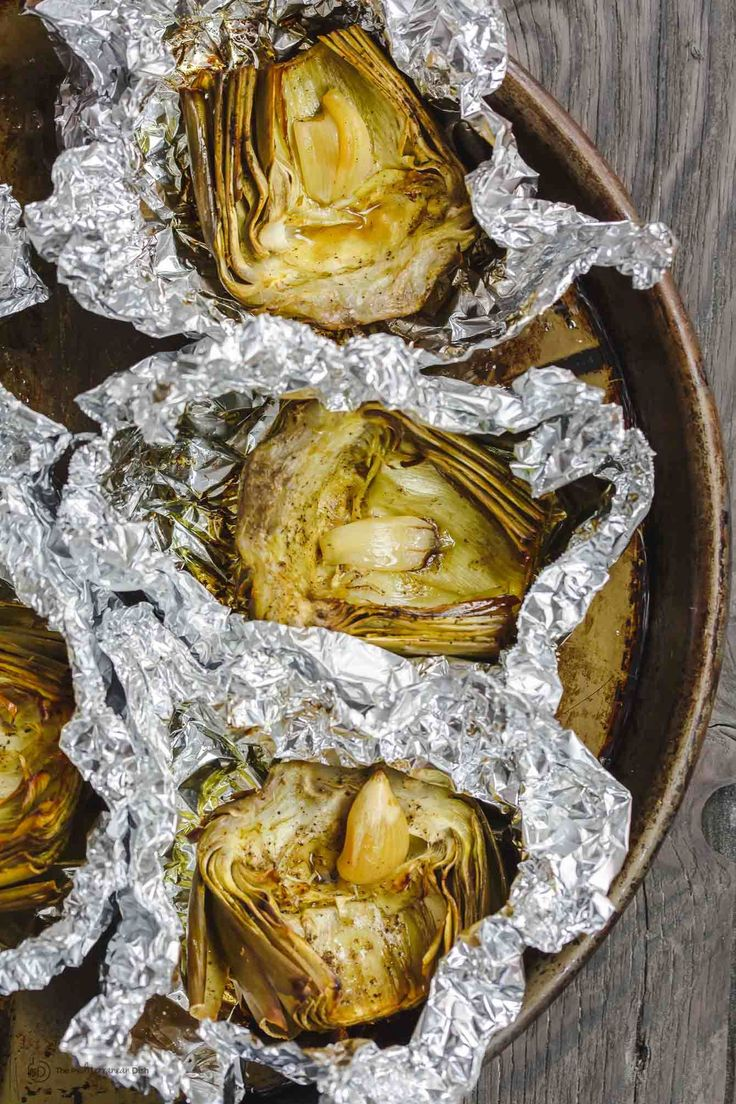 Mediterranean Roasted Artichoke Recipe | The Mediterranean Dish. Perfectly tender roasted artichoke with olive oil and a tangy roasted garlic vinaigrette! And Mediterranean favorites like capers and feta. Get the simple recipe at TheMediterraneanDish.com